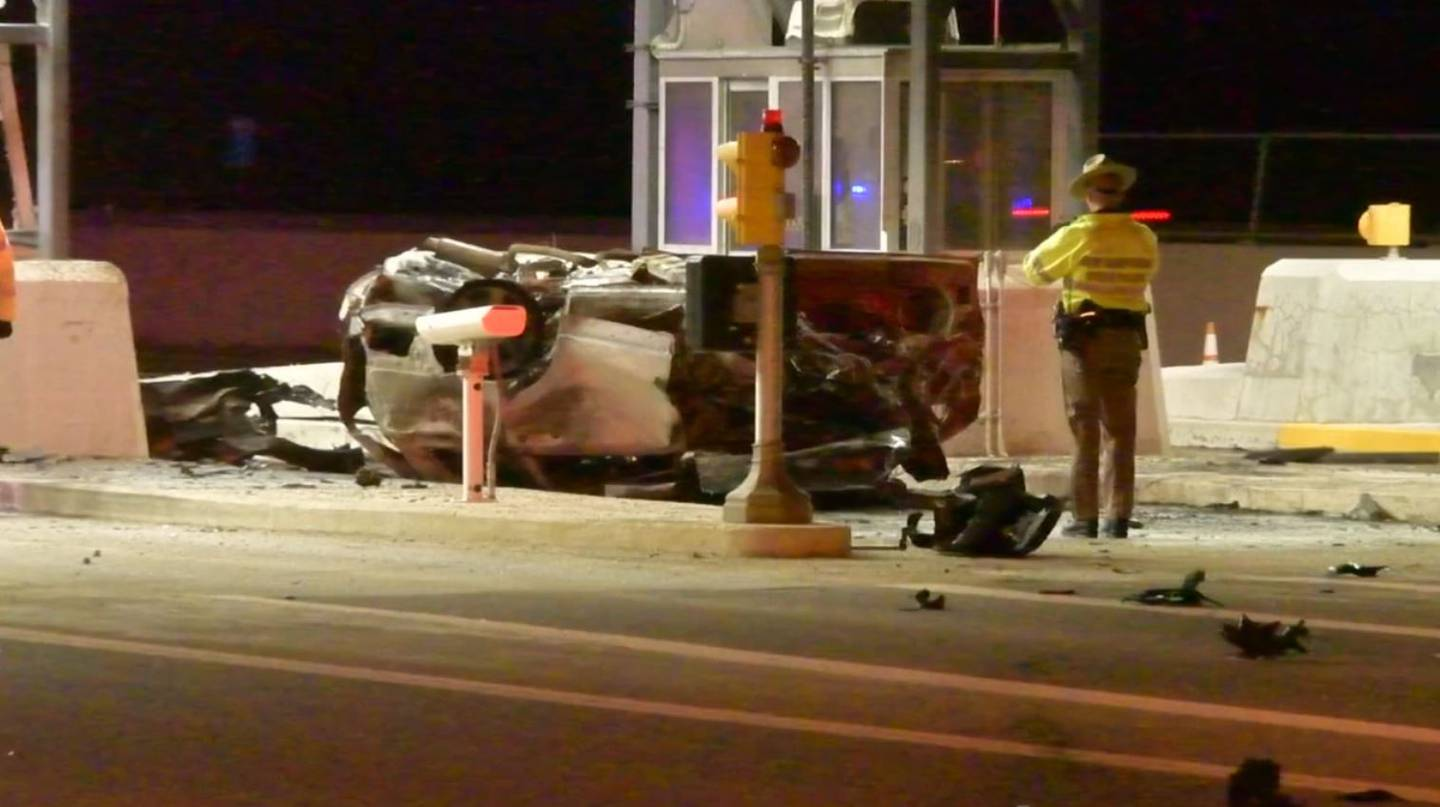 Police said the car caught fire after crashing into a toll booth that had an attendant inside. The attendant was not injured.