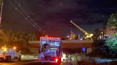 One person dead, another hospitalized after tow truck crashes, dangles off overpass in Milford